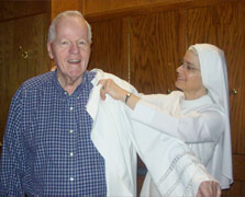 Oblate sister helping priest with his robe