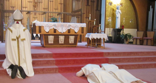 Priest and nun kneeling in a church during service